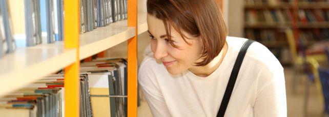 mulher biblioteca procurando livro